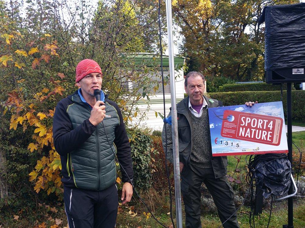 Organisator Winfried overhandigt een cheque aan Staatsbosbeheer.